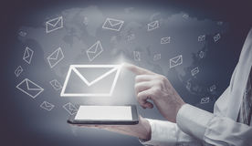 The concept of email marketing. Businessman makes sending emails from your tablet.  Stock Image