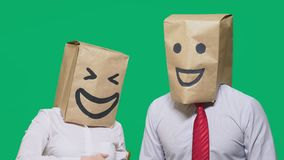 Concept of emotions, gestures. a couple of people with bags on their heads, with a painted emoticon, smile, joy, laugh. Concept of emotions, gestures. a couple stock video