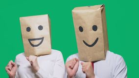 Concept of emotions, gestures. a couple of people with bags on their heads, with a painted emoticon, smile, joy, laugh. Concept of emotions, gestures. a couple stock footage