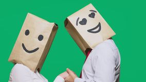 Concept of emotions, gestures. a couple of people with paper bags on their heads, with a painted emoticon, smile, joy. Eyes in love stock video footage