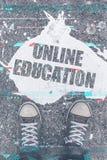 Concept en ligne d'éducation avec des pieds d'étudiant masculin sur la rue Photo libre de droits