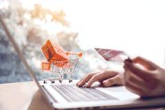 Concept en ligne d'achats avec la main de femme utilisant l'ordinateur portable et le regard Image stock