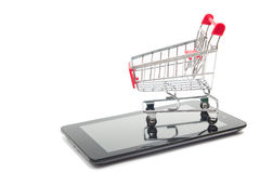 Concept en ligne d'achats - caddie, ordinateur portable et PC vides de comprimé, smartphone sur le fond blanc Copiez l'espace Image libre de droits