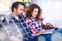 Concept en ligne d'achats - couple gai recherchant le gi de Noël Image stock