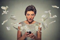 Concept en ligne d'opérations bancaires Femme choquée employant des billets d'un dollar de smartphone volant loin Photographie stock