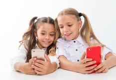 Concept en ligne de la vie Les élèves mignons d'écolières utilisent le grand écran diagonal de smartphones pour vérifier les rése images stock