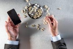 Concept en ligne de pharmacie - mains d'homme d'affaires tenant le téléphone pour commander des drogues Image libre de droits