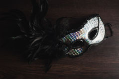 The concept of the end of the holiday, Mardi Gras. Mask with black feathers on a wooden background, a photo in low key, the concept of the end of the holiday royalty free stock images