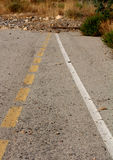 Concept - The End of the Road. A broken yellow line and a white line converging at an area with rubble. Concept - the end of the road. Going Nowhere royalty free stock image