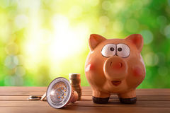 Concept of energy saving and efficiency with led bulb. Coins and piggy bank on wooden table and nature background with bokeh. Horizontal composition. Front stock photo