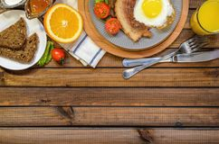 The concept of the English Breakfast: fried egg with bacon, orange juice and vegetables. Free space for text, top view royalty free stock photography