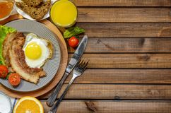 The concept of the English Breakfast: fried egg with bacon, orange juice and vegetables. Free space for text, top view royalty free stock photos