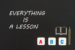Abc letters and chipboard miniature on blackboard with text everything is a lesson. Concept english school, text everything is a lesson, abc letters, chipboard Royalty Free Stock Images