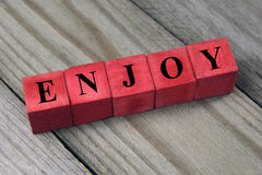 Concept of enjoy, word on wooden blocks Royalty Free Stock Images