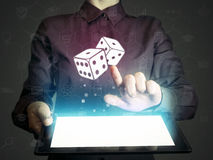 Concept of entertainment, gambling, fortune. Image of a girl with tablet pc in her hands and dice icon. Concept of entertainment, gambling, fortune Royalty Free Stock Photos