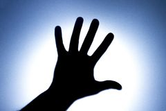 Silhouette of five fingers on a man`s hand with a bright light spot. The concept of entreaty for help or greetings. Blue. The concept of entreaty for help or royalty free stock photography