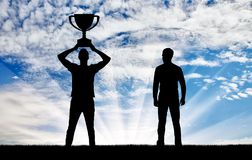 Concept of envy success of others. A man with a trophy in his hand and a man next to him who is envious. The concept of envy success of others Royalty Free Stock Image