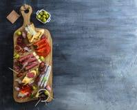 Concept espagnol typique de tapas incluez le jamon de tranches de variété, chorizo, le salami, cuvettes avec des olives, poivrons Images libres de droits
