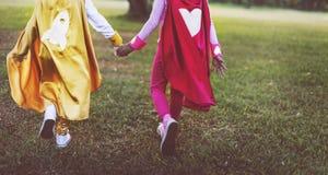 Concept espiègle d'amusement mignon de bonheur d'amitié de filles de super héros Photos stock