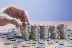 Concept et main d'argent d'économie mettant la pile de pièce de monnaie d'argent Images libres de droits