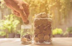 Concept et main d'argent d'économie mettant l'argent dans l'élevage de bouteille Photos libres de droits