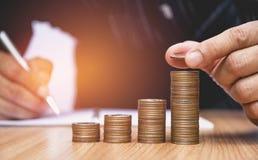 Concept et main d'argent d'économie mettant la pile de pièce de monnaie d'argent Photographie stock