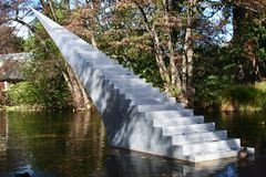 Concept of eternity and infinity. Stairs sculpture with pointy tip entitled Diminish and Ascend rising from water to air. Stairway to heaven in wilderness stock photos
