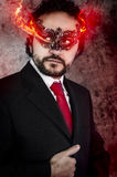 Concept evil man with fiery eyes and Venetian mask wearing black. Dress, office Royalty Free Stock Images