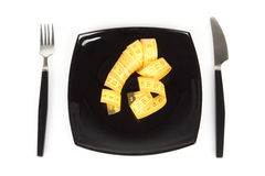 Concept of extreme dieting. Empty dish and measuring tape Stock Photos