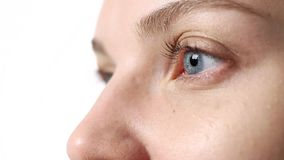 The concept of eye health and vision correction. Close - up of the blue eye of a young woman without makeup, selective focus, blinking look to the side. The stock footage
