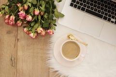 Concept féminin de lieu de travail Espace de travail indépendant avec l'ordinateur portable, roses de fleurs Fonctionnement de Bl Photo stock