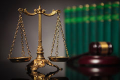 Concept of fair law and justice. Golden balanced scale in front of law books and judge's hammer Royalty Free Stock Photo