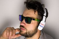 Man with white headphones with inscription FAKE NEWS stock photos
