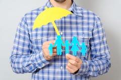 Concept familieverzekering met paraplu die een familie beschermen Royalty-vrije Stock Foto's
