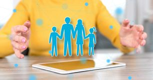 Concept of family. Digital tablet with family concept between hands of a woman in background royalty free stock photo