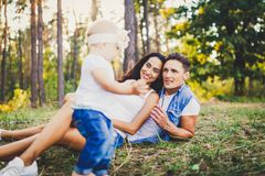 Concept of a family vacation in a park in nature. Young stylishly dressed family father and mother lie on the green grass and watc. H the first steps of the Royalty Free Stock Image