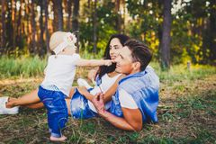 Concept of a family vacation in a park in nature. Young stylishly dressed family father and mother lie on the green grass and watc. H the first steps of the Royalty Free Stock Images