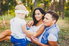 Concept of a family vacation in a park in nature. Young stylishly dressed family father and mother lie on the green grass and watc. H the first steps of the Stock Photos