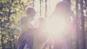 Concept of family values and happiness - young family with two k. Ids in a forested area enjoying a day together backlit by a beautiful evening sun. With a retro Stock Photos