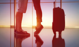 Concept of farewells and meetings. Woman standing on tiptoe beside her man. the embrace of men and women in the airport. the concept of farewells and meetings royalty free stock photography