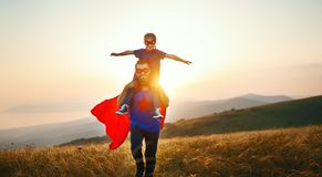 Concept of father`s day. dad and child daughter in hero superhero costume at sunset. In nature royalty free stock photography