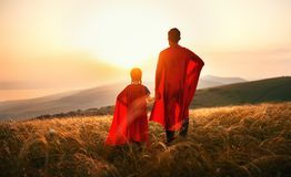 Concept of father`s day. dad and child daughter in hero superhero costume at sunset. In nature stock image