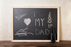 Concept of Father`s Day with handwritten text I love my Dad, pi. Ctured airplane, tank, rocket on blackboard over wooden background and toy stock images
