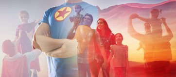 Concept of father`s day. ! Man in superhero costume is protecting his family royalty free stock photo