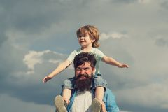 Concept of Fathers day. Father and son together. Cute boy with dad playing outdoor. Enjoy. Childhood. Father giving son. Ride on back in park. Generation royalty free stock images