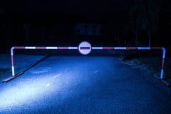 Concept faux de manière Barrière avec le signe aucune entrée la nuit Barrière se tenant sur la route au bâtiment hanté effrayant  photographie stock