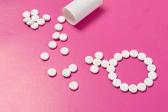 Concept Female health. Gender symbol made from pink pills or tablets on pink background. Concept Female health, female contraception. Gender symbol made from royalty free stock image