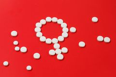 Concept Female health. Gender symbol made from white pills tablets red background. Concept Female health. Gender symbol made from white pills or tablets on red stock photography