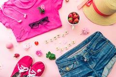 Concept femelle de planification d'été - habillement, accessoires, fleurs et fraises sur le fond rose Style de mode - T-shirt, de Photographie stock libre de droits