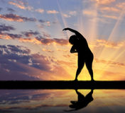 Concept of fight against obesity and overweight. Silhouette of a fat woman is doing exercises, and its reflection in water Stock Photography